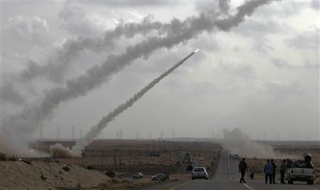 Rebel fighters fire rockets from the desert east of Brega April 6, 2011. REUTERS Youssef Boudlal
