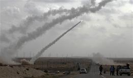 <p>Rebel fighters fire rockets from the desert east of Brega April 6, 2011. REUTERS Youssef Boudlal</p>