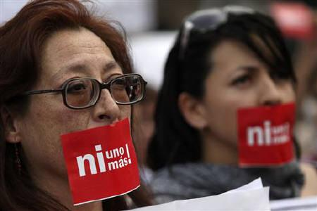 People participate in a march in Mexico City called out by poet Javier Sicilia after the death of his son whose body was found along with six other dead people inside a car a week ago in Cuernavaca, April 6, 2011. The stickers read ''Not one more.'' REUTERS/Carlos Jasso