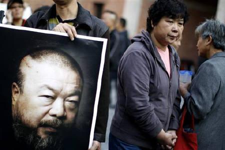 A supporter of prominent Chinese artist Ai Weiwei holds a picture of him at Weiwei's art studio in Shanghai November 7, 2010. REUTERS/Carlos Barria/Files