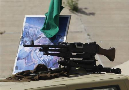 A weapon is seen next to a poster of a Libyan leader Muammar Gaddafi on top of an Army vehicle as the vehicle escorts a bus on its way to the Roman ruins in Sabratha, about 75 km (47 miles) west of Tripoli, April 1, 2011. REUTERS/Zohra Bensemra