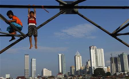 Children play at an electricity pylon in Jakarta, February 11, 2011. REUTERS/Beawiharta