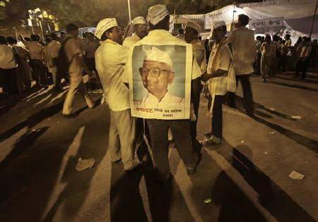 A supporter wearing a paper poster of social activist Anna Hazare attends a protest against corruption in New Delhi April 7, 2011. REUTERS/Adnan Abidi