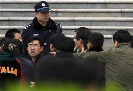 Uniformed and plainclothes police surround a man at the site of a proposed church gathering at a shopping area in Beijing April 10, 2011. REUTERS/David Gray