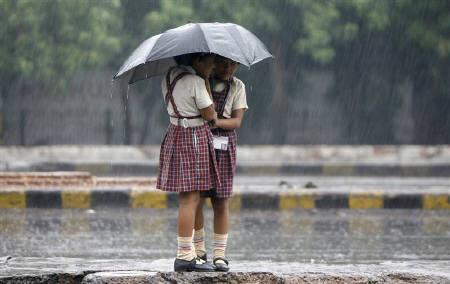 Schoolgirls stand on a road divider as they huddle under an umbrella during monsoon rain in New Delhi September 10, 2009. REUTERS/Adnan Abidi
