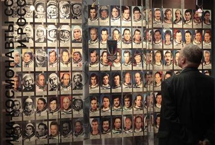 A visitor looks at a wall of photographs of cosmonauts on display during the opening of an exhibition at the Memorial Museum of Astronautics in Moscow, April 8, 2011. REUTERS/Alexander Natruskin