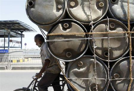A man rides his trishaw loaded with empty plastic barrels which are used to carry oil in Ahmedabad March 10, 2011. REUTERS/Amit Dave/Files