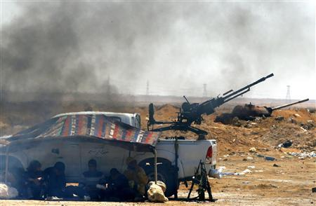 Rebel fighters rest by their pick-up truck with a mounted anti-aircraft gun, along the frontline at the western entrance of Ajdabiyah April 13, 2011. REUTERS/Yannis Behrakis