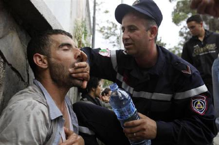 A rescuer assists a university student during a demonstration in Algiers April 12, 2011. REUTERS/Ramzi Boudina