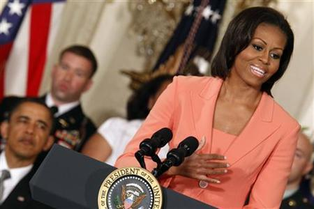 U.S. President Barack Obama (L) listens as first lady Michelle Obama speaks during the launch of ''Joining Forces'', a national initiative in support of service members and their families, at the White House in Washington April 12, 2011. REUTERS/Kevin Lamarque