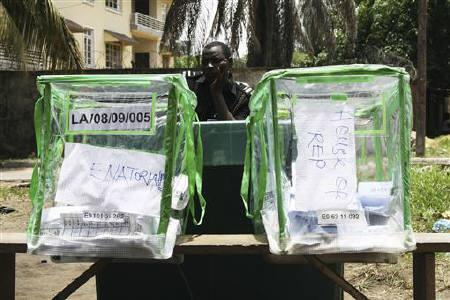 A Nigerian police officer watches over ballot boxes in Ikoyi, Lagos, April 9, 2011. REUTERS/Nick Tattersall