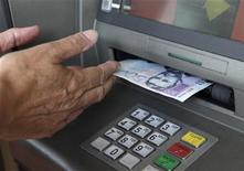 <p>A customer withdraws 500 Estonian kroon ($40) from an ATM in Tallinn July 13, 2010. REUTERS/Ints Kalnins</p>