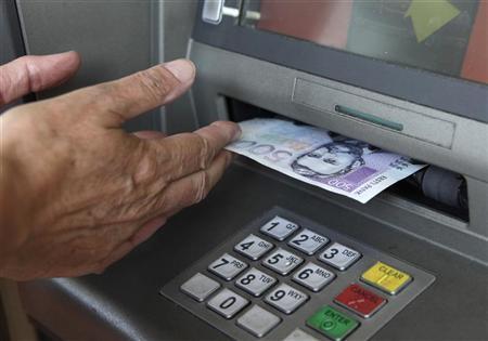 A customer withdraws 500 Estonian kroon ($40) from an ATM in Tallinn July 13, 2010. REUTERS/Ints Kalnins