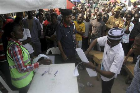 People watch as electoral officers count the ballots after voting ended at a polling centre in Nigeria's commercial capital Lagos April 16, 2011.  REUTERS/Akintunde Akinleye