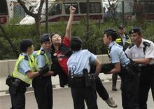<p>Policiais retiram manifestante pró-democracia que tentou atravessar a barricada da polícia em frente ao escritório de representação da China em Hong Kong. A polícia entrou em atrito neste domingo com simpatizantes do artista chinês Ai Weiwei, que está preso pelas autoridades chineses. REUTERS/Tyrone Siu</p>