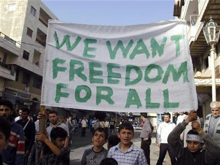 Boys hold a banner during a demonstration in the the Syrian port city of Banias April 17, 2011. REUTERS/Stringer