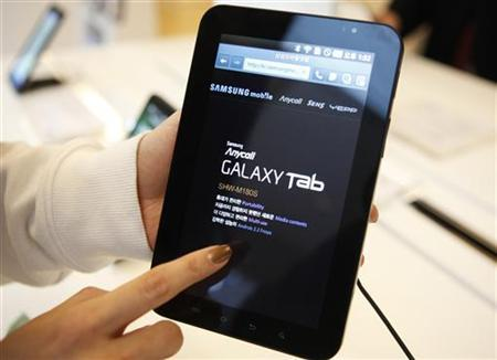 An employee of Samsung Electronics demonstrates Samsung's Galaxy Tab tablet during a photo opportunity at a showroom of the company in Seoul January 18, 2011. REUTERS/Lee Jae-Won