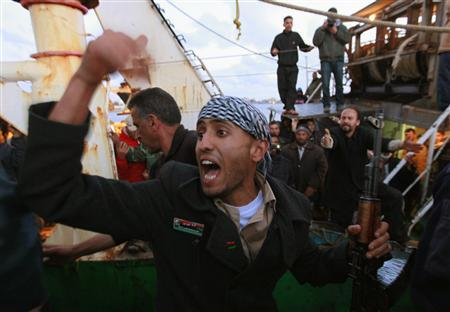 A rebel fighter shouts at onlookers to move away in order to let Libyan civilians being evacuated by a fishing boat from Misrata to disembark at the port of Benghazi April 18, 2011. REUTERS/Yannis Behrakis