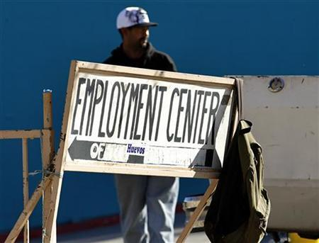 A day laborer stands behind a sign for an employment center in San Diego, January 6, 2011. REUTERS/Mike Blake
