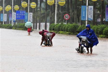 Residents make their way on a flooded street in Qionghai, Hainan province, October 17, 2010. REUTERS/China Daily