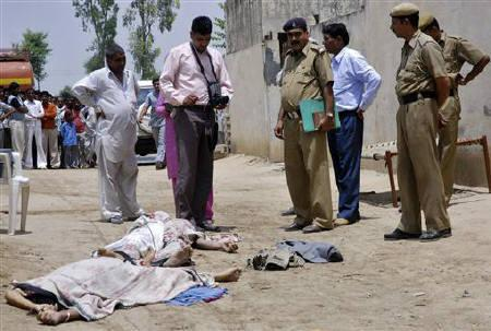 Police look at the bodies of Sunita Devi (bottom L), 21, and her partner Jasbir Singh, 22, after they were killed by villagers in an ''honour killing'' in Ballah village in the northern Indian state of Haryana May 9, 2008. REUTERS/Stringer/Files