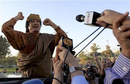 Libyan leader Muammar Gaddafi gestures as he is surrounded by members of the media, at his Bab al-Aziziyah compound in Tripoli, April 10, 2011. REUTERS/Zohra Bensemra