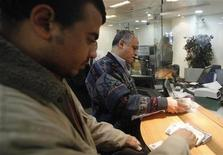 <p>Customers count their money at a bank in Cairo February 20, 2011. REUTERS/Suhaib Salem</p>