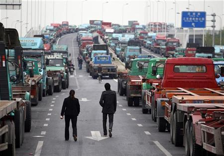 People walk along an unfinished road being used by truck drivers to park their container trucks near a port in Shanghai April 21, 2011, following a protest nearby the area earlier in the morning. REUTERS/Carlos Barria