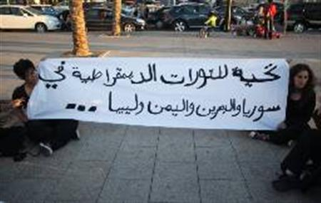 Students hold a banner in a support of Syrian demonstrators during a sit-in in Beirut April 20, 2011. The banner reads in Arabic, '' A salute to the democratic revolutions''. REUTERS/Mohamed Azakir