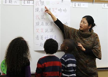 Teacher Kennis Wong (R) points to Chinese characters on a board at Broadway Elementary School in Venice, Los Angeles, California, April 11, 2011. REUTERS/Lucy Nicholson