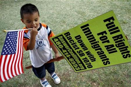 A boy holds a flag and sign outside the Arizona's State Capital in Phoenix, July 28, 2010. REUTERS/Joshua Lott