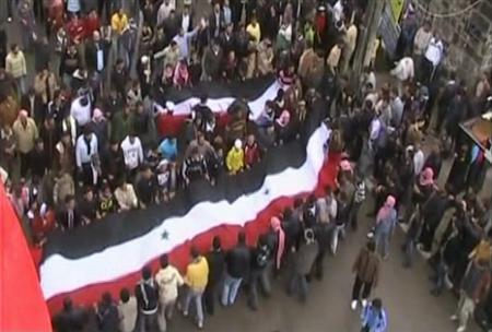 A still image taken from an amateur video on April 22, 2011 shows protesters holding a large Syrian flag during a demonstration in Deraa. REUTERS/Amateur video via Reuters TV