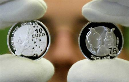 A Belgian central bank employee displays the newly minted 10-euro silver coin commemorating the 75th anniversary of Tintin in Brussels, January 8, 2003. REUTERS/Francois Lenoir/Files