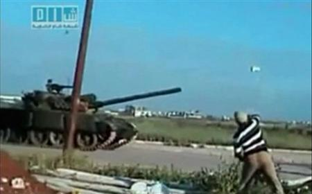 A man throws a rock at a passing tank in a location given as Deraa on April 25, 2011, in this still image from an amateur video. REUTERS/Social Media Website via Reuters TV