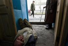 <p>A drunk man lies in the hallway of a housing estate outside the Siberian city of Tomsk some 3500 km (2175 miles) east of Moscow June 5, 2008. REUTERS/Thomas Peter</p>
