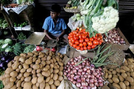 A vendor sits at a roadside vegetable shop in Kolkata August 2, 2006. REUTERS/Parth Sanyal/Files