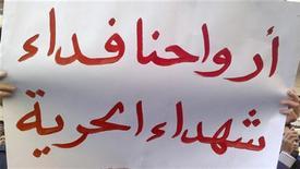 """<p>Демонстрант держит плакат с надписью """"Пожертвуйте ваши жизни, мученики свободы"""" в сирийском городе Банияс 26 апреля 2011 года. Верные президенту Сирии Башару аль-Ассаду войска в ночь на среду заняли пригород столицы страны Дамаска, в то время как в центре антиправительственных выступлений - городе Дераа - уже стоят танки. REUTERS/Handout</p>"""