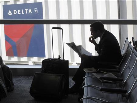 A passenger waits for his flight near a Delta Air Lines logo at Detriot Airport November 20, 2010. REUTERS/Sim Wei Yang