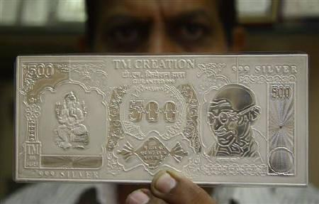 A jeweller displays a silver plate in the form of a rupee note in Chandigarh October 10, 2009. REUTERS/Ajay Verma/Files