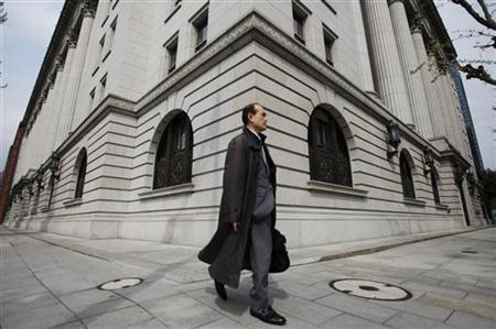 A man walks past insurance company building in Tokyo April 21, 2011. REUTERS/Yuriko Nakao