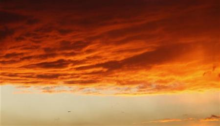 An airplane flies under a cloud formation at sunset in Los Angeles September 29, 2010. REUTERS/Mario Anzuoni