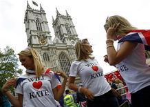 <p>Fãs da família real britânica ajustam bandeiras sobre seus ombros, em frente à Abadia de Westminster, em Londres. Apesar de aumentar a venda de suvenires, o casamento do príncipe William com Kate Middleton não deve gerar o impulso esperado pelo governo para a economia da Grã-Bretanha. 28/04/2011 REUTERS/Kai Pfaffenbach</p>