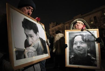 Protesters hold portraits of human rights lawyer Stanislav Markelov and opposition journalist Anastasia Baburova during an anti-fascist rally in central Moscow January 19, 2011. REUTERS/Sergei Karpukhin