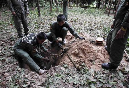 Thai anti-explosive officers remove the shells of explosives found in a rubber plantation at Hua Ang village in Surin province on the border between Thailand and Cambodia April 29, 2011. One Thai soldier died and four were wounded in further clashes overnight on a disputed stretch of border between Thailand and Cambodia, a Thai military spokesman said on Friday, as a ceasefire agreed the previous day failed to hold. REUTERS/Sukree Sukplang