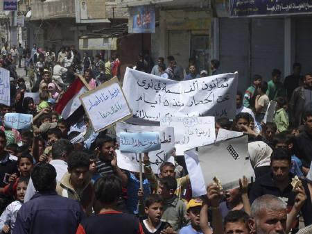 Protesters gather during a demonstration in the southern town of Nawa, near Deraa April 27, 2011. Banner reads: ''80,000 citizens of Mawa are under siege since five days''.  27, 2011. REUTERS/Handout