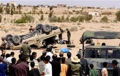 <p>Солдаты армии Туниса, жители тунисского города Дехиба и ливийские беженцы стоят возле перевернувшегося автомобиля, принадлежавшего войскам Муаммара Каддафи, Дехиба, 29 апреля 2011 года. Сторонники ливийского лидера Муаммара Каддафи пересекли границу с соседним Тунисом и столкнулись с тунисскими вооруженными силами в пограничном городе Дехиба в пятницу, тем самым перетащив внутренний конфликт за пределы страны. REUTERS/Anis Mili</p>