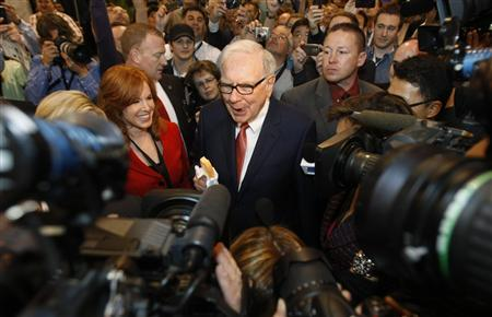 Berkshire Hathaway Chairman Warren Buffett, holding an ice cream bar, is surrounded by press, shareholders and security as he wanders the company trade show before his company's annual meeting in Omaha, Nebraska April 30, 2011. REUTERS/Rick Wilking