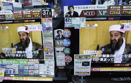 A man is seen between TV screens showing news that a U.S.-led operation had killed al Qaeda leader Osama bin Laden, at an electronic shop in Tokyo May 2, 2011. REUTERS/Issei Kato