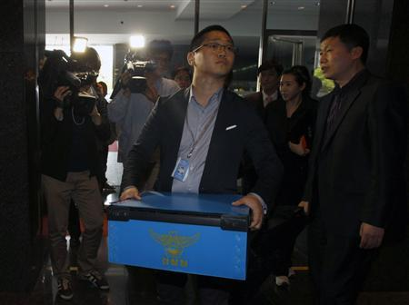 A policeman carries a box containing confiscated goods at Google Inc's office in Seoul May 3, 2011. Google Inc's Seoul office was raided on Tuesday on suspicion the Internet search firm's mobile advertising unit AdMob had illegally collected location data, South Korean police said, the latest setback to Google's Korean operations. The probe into suspected collection of data on where a user is located without consent highlights growing concerns about possible misuse of private information as the use of mobile devices such as smartphones and tablets increases. REUTERS/Truth Leem