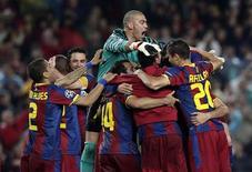 <p>Jogadores do Barcelona comemoram classificação na Liga dos Campeões, após empate com o Real Madrid. REUTERS/Albert Gea</p>